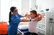 Leinwandbild Motiv Gentle dark-haired Asian doctor correcting posture of little kid