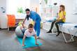 Leinwandbild Motiv Hard-working little boy leaning on a grey pilates ball