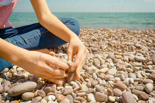 Poster de jardin Zen pierres a sable Teenager sitting on a pebble. Hand put a stone on laying stones on the shore of the blue sea.