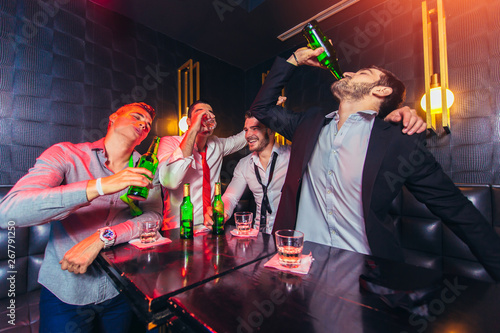 Fotografering  Group of smiling male friends having fun in night club
