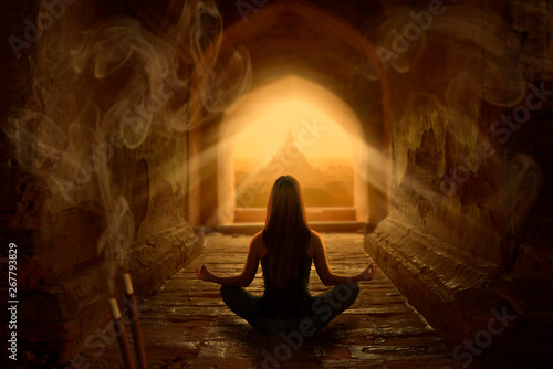 Woman meditating in buddhist temple