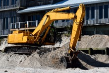 Backhoe Working To Correct Ocean Beach Erosion At Florida, USA