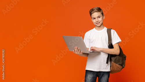 Obraz na plátně  Teenage boy with backpack using laptop, orange background