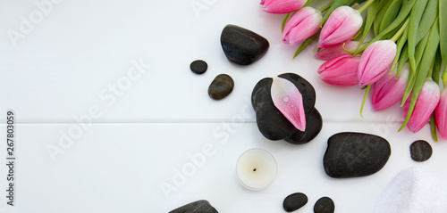 Poster Tulip Spa setting with tulips , black stones and towel on white wood background.