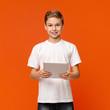 Leinwandbild Motiv Teen boy using digital tablet on orange studio background