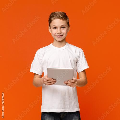 Teen boy using digital tablet on orange studio background