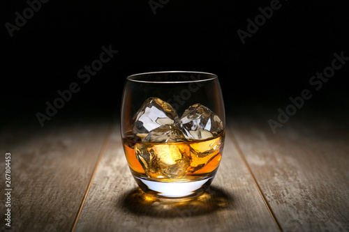 Whiskey, Rum, Cognac liquor on ice in a round rocking tumbler glass, on vintage wooden table with dark black background