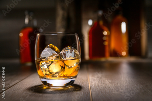 Close up of single malt scotch whiskey, craft bourbon in round tumbler glass, on the rocks, with liquor bottles and rustic background