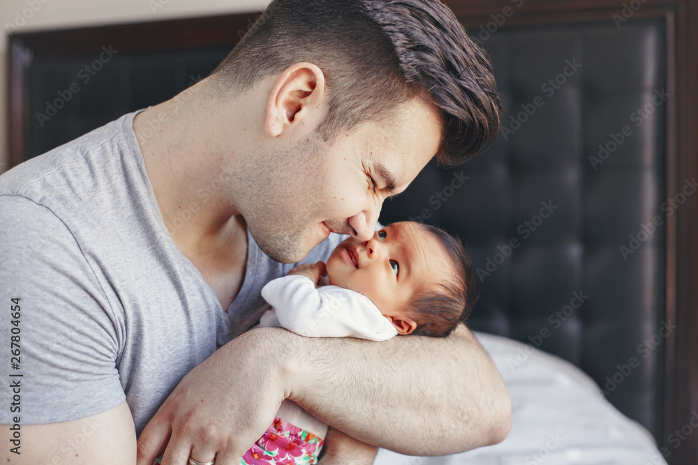 Fototapety, obrazy: Closeup of young Caucasian father with newborn mixed race Asian Chinese baby. Male man parent holding child daughter son. Authentic lifestyle touching moment. Single dad family