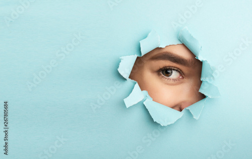 Cadres-photo bureau Fleur Nude Makeup. Female Eye With Mascara Looking Through Torn Blue Paper