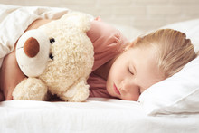 Cute Little Child Girl Sleeping With Teddy Bear In Her Bed