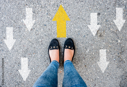 Photo  woman shoes on asphalt and opposing direction arrows on asphalt ground, personal