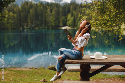 Young woman on the lake listens to music via a digital tablet - 267808450