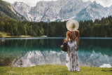 Young beautiful woman in a dress and hat near the lake - 267808809