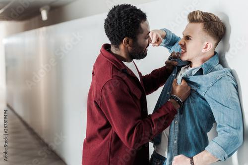 Valokuva two multiethnic students fighting in corridor in college