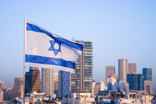 Flag Of Israel On The Background Of Modern City. Israeli Flag Against The Background Of Skyscrapers In Tel Aviv In Front Of Blue Sky.