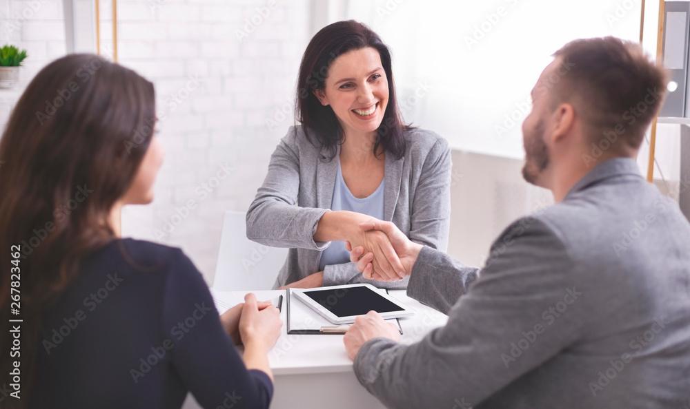 Fototapeta Smiling female insurance broker and young family shaking hands