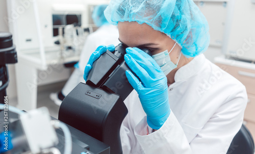 Tuinposter Hoogte schaal Woman scientist working on microscope