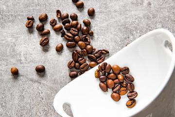 Ziarenka kawy na betonowym tle wraz z białą miską