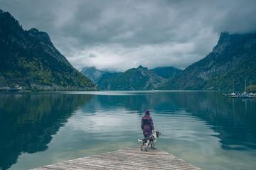 Kobieta z psem Springer Spanielem stoją na pomoście nad górskim jeziorem w pochmurny dzień