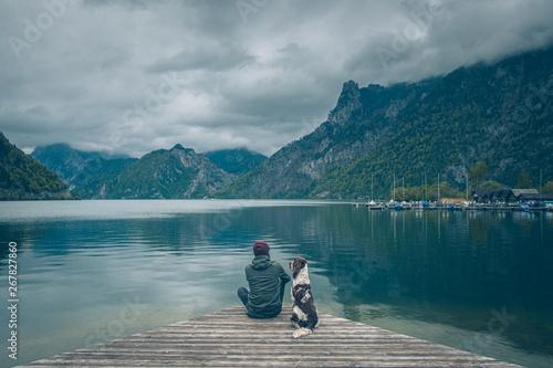 Fotografie, Obraz Mężczyzna z psem siedzą na pomoście nad jeziorem w górach w pochmurny dzień