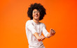 Happy african american man moving on orange background