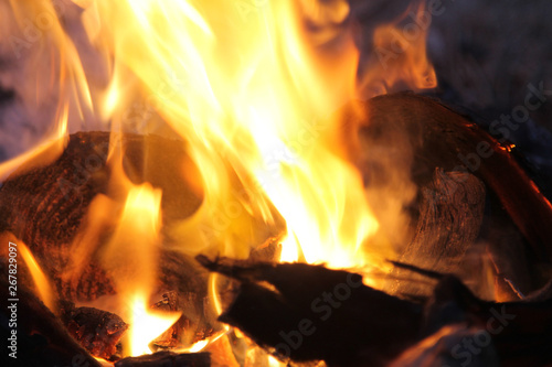 Poster Firewood texture Closeup yellow flame burning charcoal ember. Abstract Fire. Selective focus