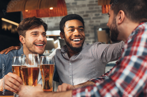 Poster de jardin Individuel Sharing News. Diverse Friends Drinking Beer In Bar