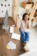 Leinwandbild Motiv Above view portrait of smiling mixed race woman speaking by phone while sitting at desk in home office with feet on table, copy space