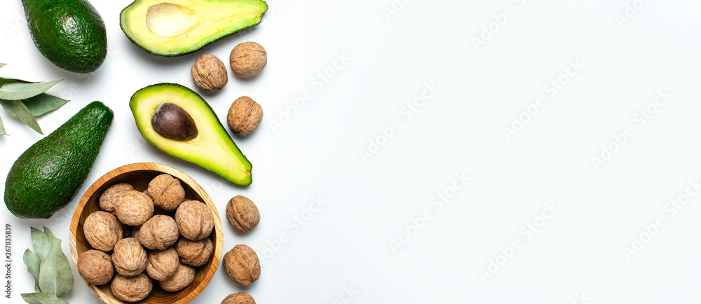 Fototapety, obrazy: Ripe fresh avocado, walnuts in wooden bowl, eucalyptus twigs on white background top view Flat lay copy space. Fruits Healthy food concept, diet, healthy lifestyle.