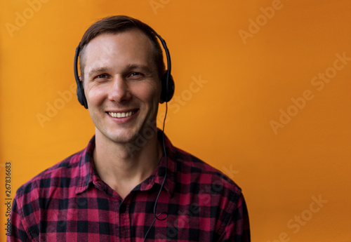 Young happy handsome man wearing headphone and enjoy music over yellow background. - 267836683