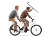 Two elderly men riding a tandem bicycle and waving with a walking cane
