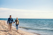 canvas print picture Young couple walking outdoors on beach, holding hands. Copy space.