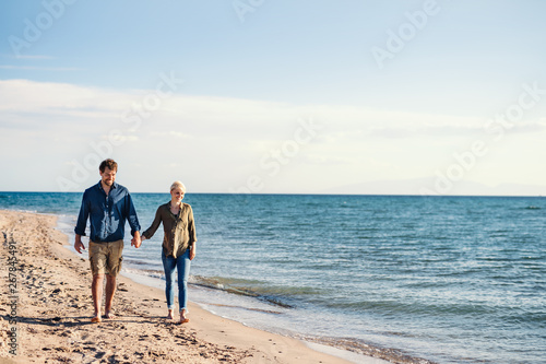 canvas print motiv - Halfpoint : Young couple walking outdoors on beach, holding hands. Copy space.