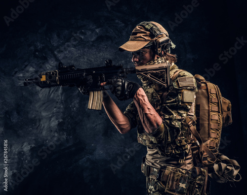 Special forces soldier in protective uniform holding an assault rifle and aim at the enemy Canvas-taulu