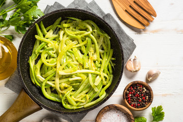 Zucchini noodles in frying pan on white.