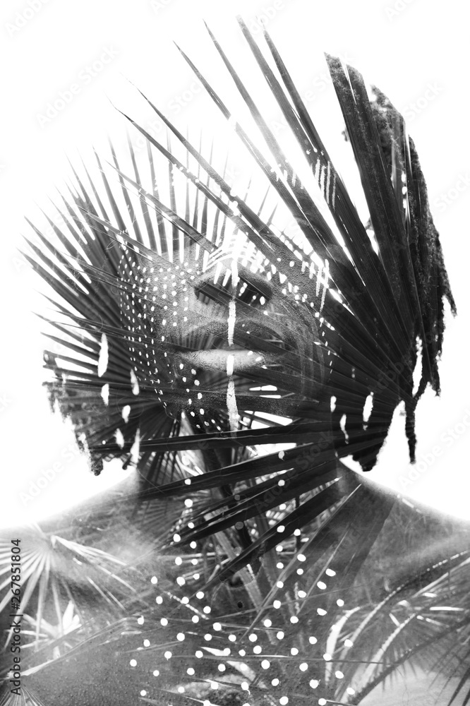 Fototapeta Double exposure of a dark skinned man with dreadlocks and face paint combined with a photograph of a beautiful lush plants in black and white