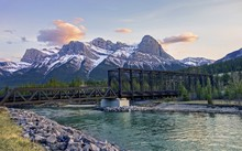 Historic Engine Bridge, A Steel Truss Pedestrian Footbridge, Over Bow River In Canmore With Snowcapped Mountain Peaks Landscape On The Horizon