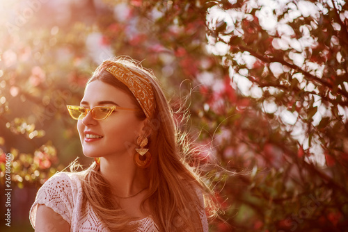 Outdoor close up portrait of young beautiful fashionable happy smiling girl with long blond hair, wearing trendy yellow headband, plastic color sunglasses, big earrings, posing at sunset Poster Mural XXL