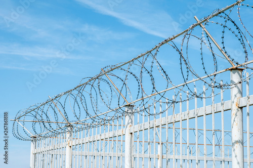 Photo  iron fence with barbed tape on blue sky