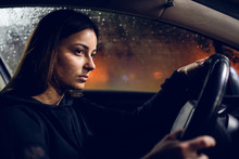 Young Woman Holding A Car Driving Wheel In A Rainy Night Rain