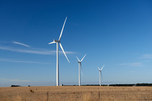 Three Wind Turbines On A Farm In An Australian Landscape.