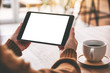 Leinwandbild Motiv Mockup image of hands holding black tablet pc with blank white screen horizontally with coffee cup on wooden table