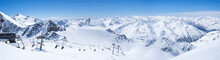Panoramic Landscape View From Top Of Wildspitz On Winter Landscape With Snow Covered Mountain Slopes And Pistes And Skiers On Chair Lift At Stubai Gletscher Ski Resort At Spring Sunny Day. Blue Sky