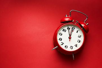 Vintage Alarm Clock On Red Background.