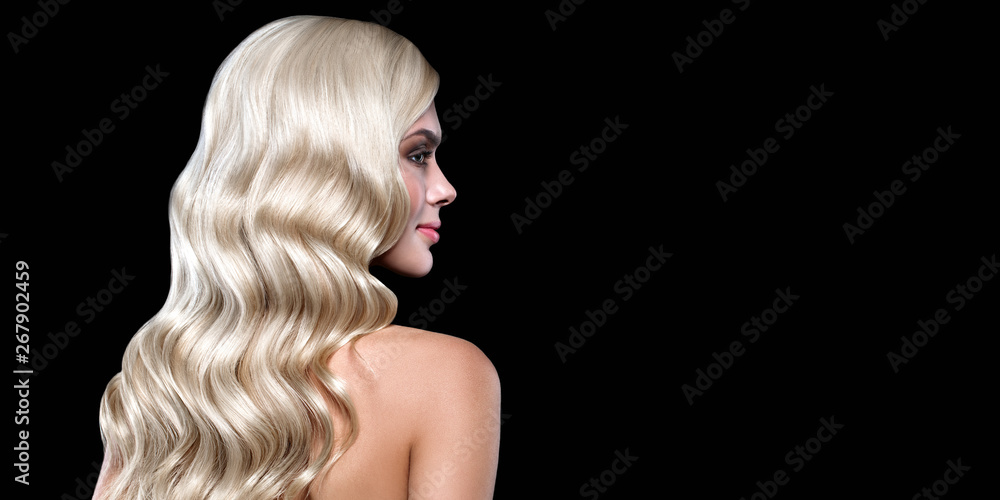Fototapeta Blonde Woman Portrait with blue eyes and Healthy Long Shiny Wavy hairstyle posing on black background. Volume shampoo. Blond Curly permed Hair and bright makeup.  Beauty salon and haircare concept.