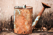 Old Watering Can On Wooden Bac...