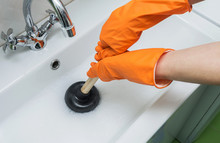 Person In Protective Orange Gloves Unblocking A Clogged Sink With Plunger Or Rubber Pump. Close-up, Selective Focus.