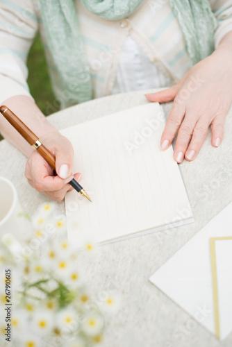 手紙を書くシニア女性の手元 Fotobehang