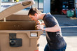 canvas print picture - Junger Mann schaut in grüne Mülltonne
